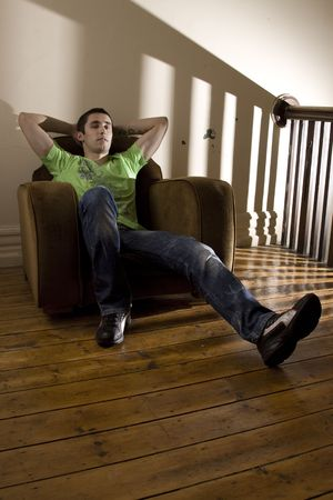 Young man lazing around in an old broken armchair