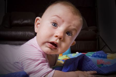 intrigued: humorous close up of a little baby crawling on the floor