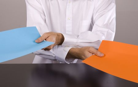 Man passing on two pieces of paper in opposite direction