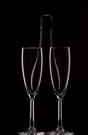 Silhouette of a champagne bottle with two glasses photo