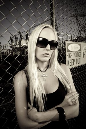 Tough chic standing against a fence at a electricity power plant photo