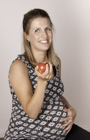 Smiling pregnant woman eating a red apple photo