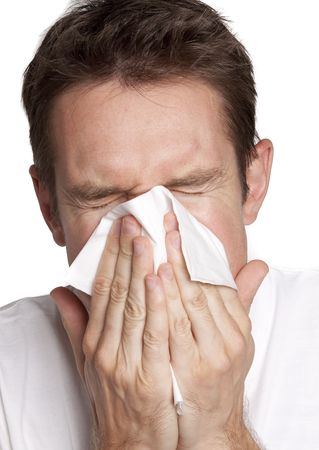 Young man blowing his nose in a tissue