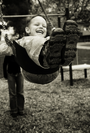 A little boy having a great time on a swing in a playground photo