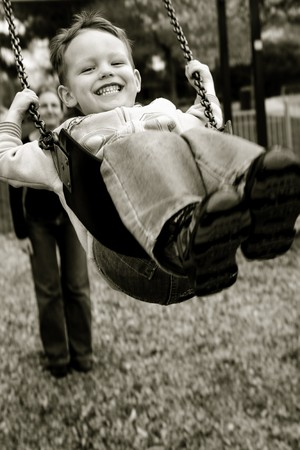 A little boy having a great time on a swing in a playground