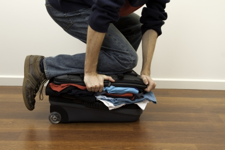 open suitcase: forcing the last few pieces of clothing into an over-full suitcase