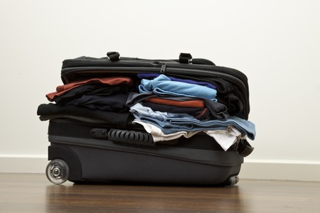 Suitcase stuffed with way to much clothes Stock Photo