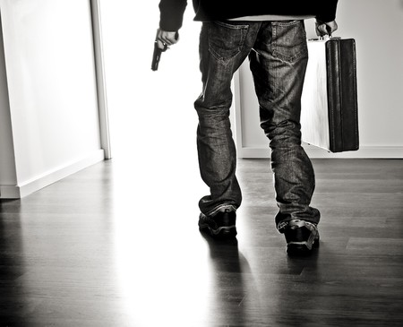 Robber walking out with a pistol and briefcase