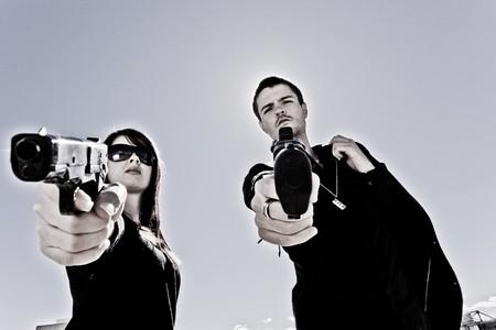 ragazza che indica: Guy e una ragazza che punta due pistole  Archivio Fotografico