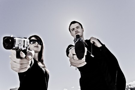 Guy and a girl pointing two guns