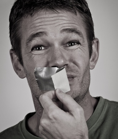 shut: Man removing tape from his mouth
