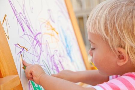 Little toddler drawing on a whiteboard Standard-Bild