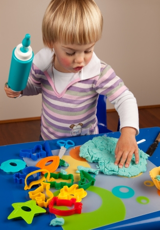 Little girl playing with play dough