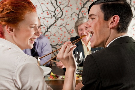 Girl feeding a guy with chopsticks photo