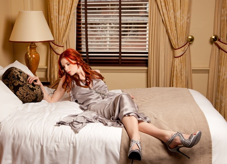 Young woman lying on her hotel bed Stock Photo