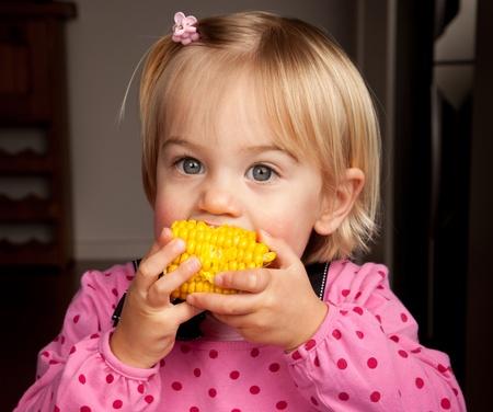 elote: Detalle de una pequeña niña teniendo un mordisco de maíz en la cob