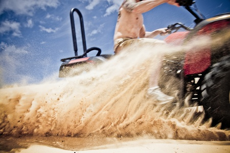 Quad bike speeding by on the sand Stock Photo - 11236176