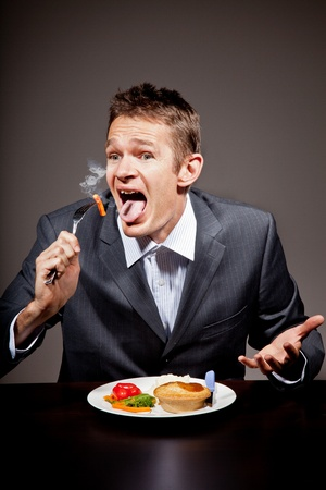 burning man: MAn burning his mouth on hot food Stock Photo