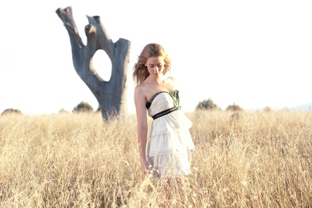 young woman standing in a field of long grass