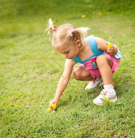 Little girl picking some yellow flowers in the garden photo