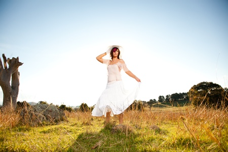 twirls: Young woman dancing in a field Stock Photo