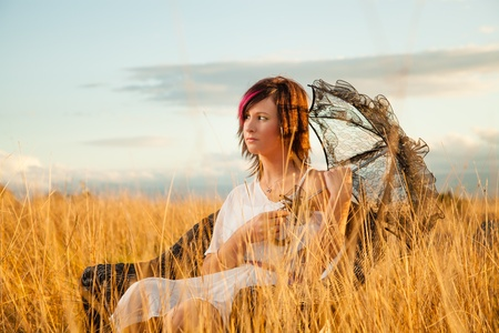young woman with umbrella sitting on a chair in a field photo