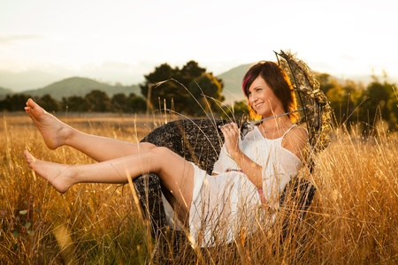 young woman sitting in a field with an umbrella Stock Photo - 13423631