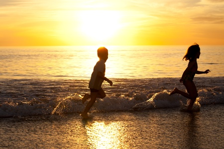 Two kids running in the white wash of the beach
