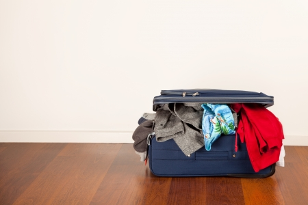 overflow: A suitcase overflowing with clothes Stock Photo