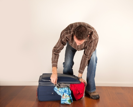 forcing the last few pieces of clothing into an over-full suitcase  photo