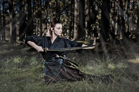 Female samurai warrior in an attacking stance photo