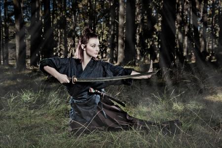 attacking: Guerrero samurai femenina en una posici�n de ataque Foto de archivo