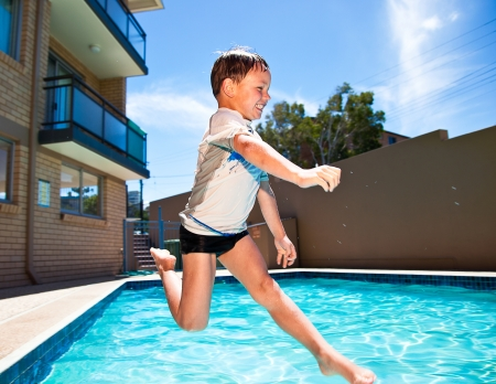 Little kid jumping into a swimming pool photo