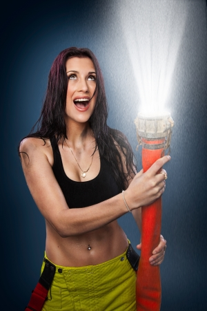 Young woman spraying water in the air with a fire hose photo