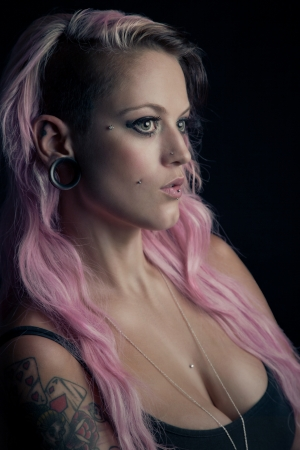 Rebellious looking girl with pink hair and piercings