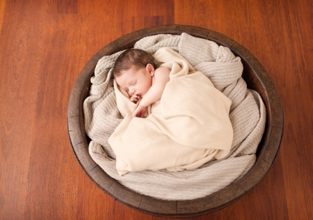 Little newborn baby in a wooden bowl