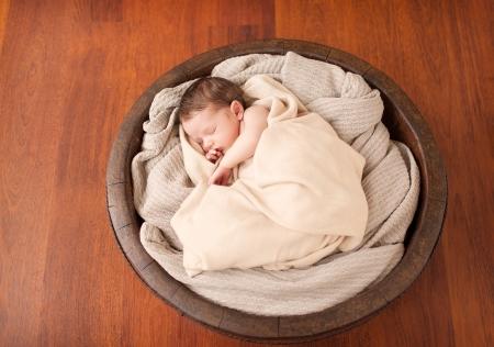 Little newborn baby in a wooden bowl