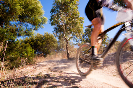 mountain bicycling: Mountain bike racer zooming past, with motion blur