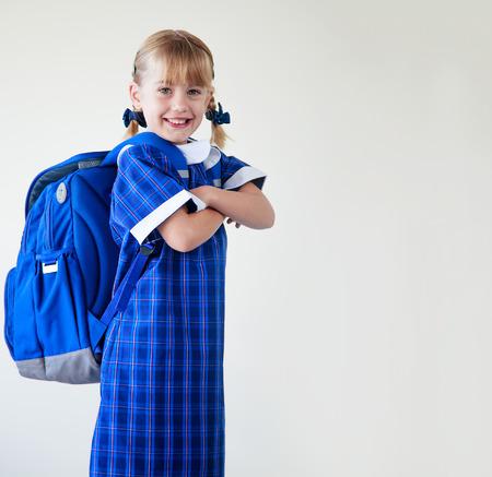 schoolgirl in uniform: Little girl dressed in her school uniform and backpack ready to go to school Stock Photo