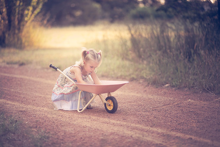 Little girl playing in a park with a wheelbarrow