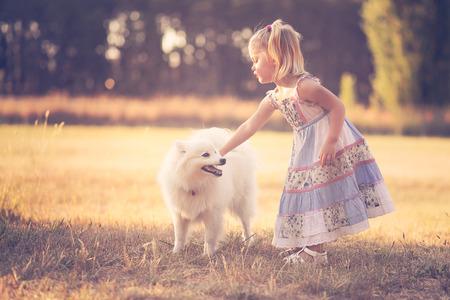niño empujando: Niña que juega con un perro en un parque Foto de archivo