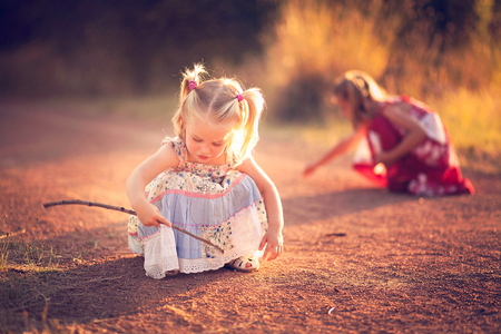 Little girl playing in the dirt with a stick Stock Photo