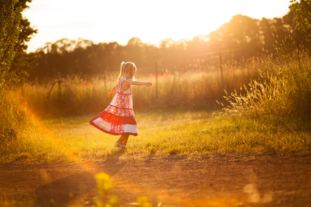 Little girl twirling in the sun Stock Photo