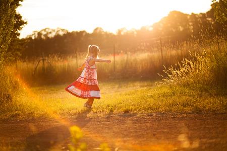 overexposed: Little girl twirling in the sun Stock Photo