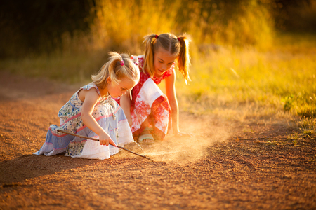 Two sisters playing in the dirt photo