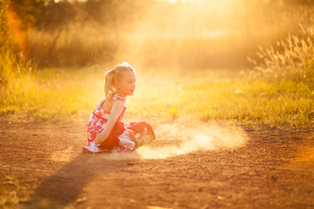 little girl playing in the dust with a stick photo