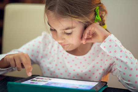 Little girl playing on her tablet at home photo