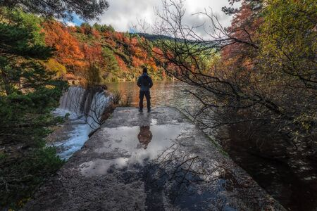 A man observes a waterfall from a dam in autumn