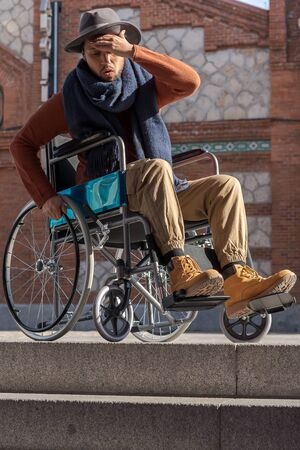 Young paralyzed Latino man in a wheelchair on the street wearing a frustrated and indignant hat in front of some stairs he can't go down Banque d'images - 143478228