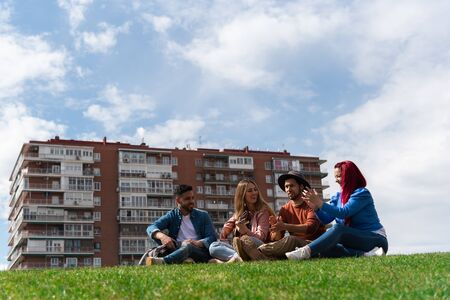 Two young Hispanic men enjoy music with a guitar next to two Caucasian girls in a city park, image includes space for text 版權商用圖片